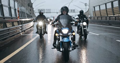 A Group Of Bikers Riding On Wet Road