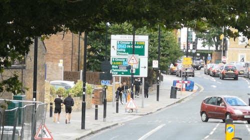 People Walking and Jogging on Sidewalk