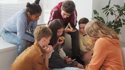 青少年在吃披萨时看着智能手机