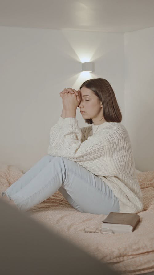 Woman in White Knitted Sweater Praying