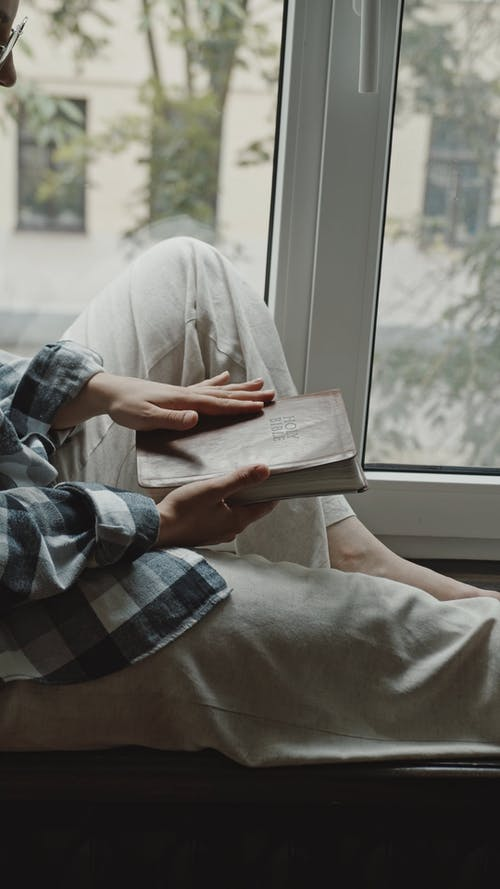 Woman Sitting by the Window While Reading Her Bible