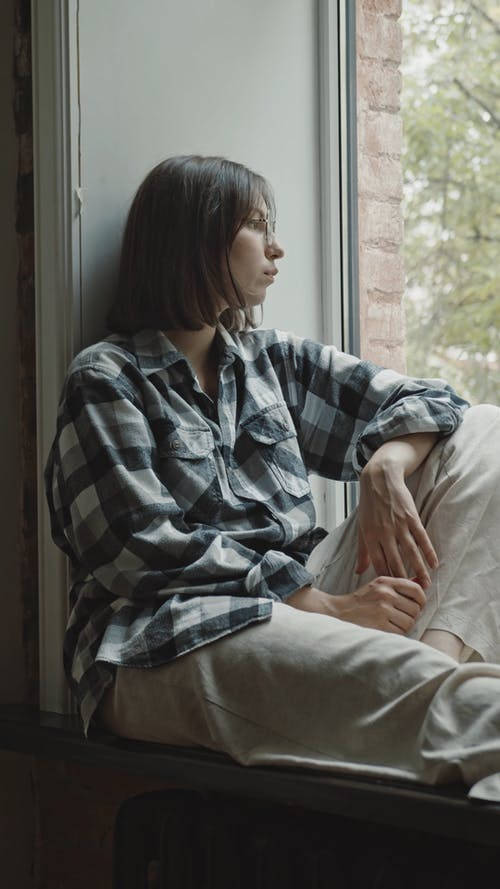 Woman in Plaid Dress Shirt Sitting by the Window