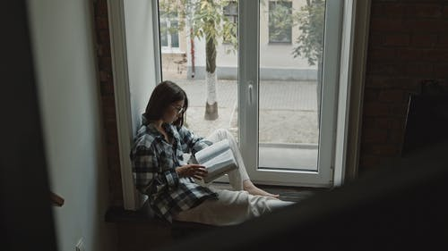 Woman in Plaid Shirt Sitting by the Window While Reading a Bible