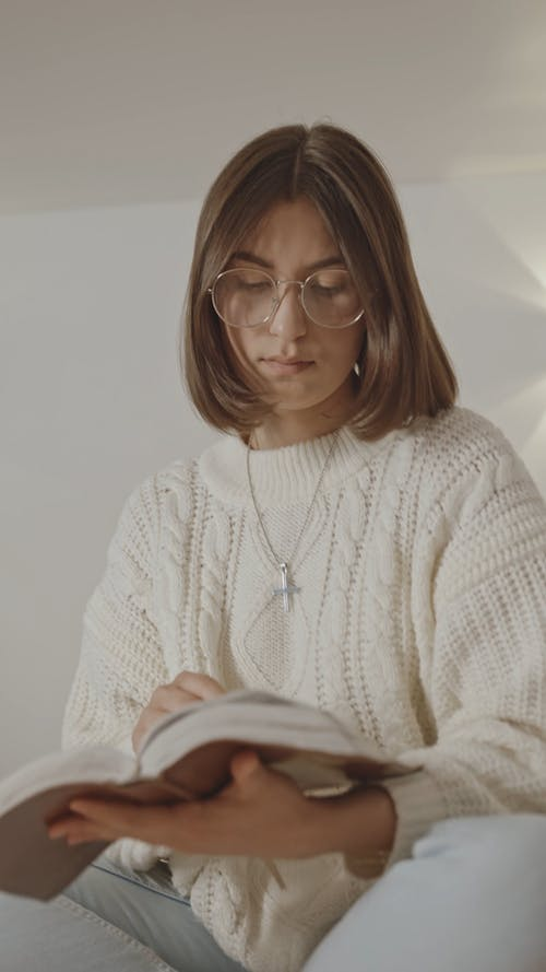 Woman in White Sweater Reading a Book