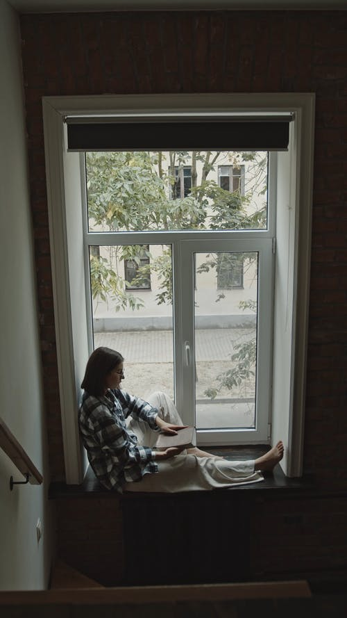 High Angle Shot of Woman Sitting by the Window While Reading a Bible