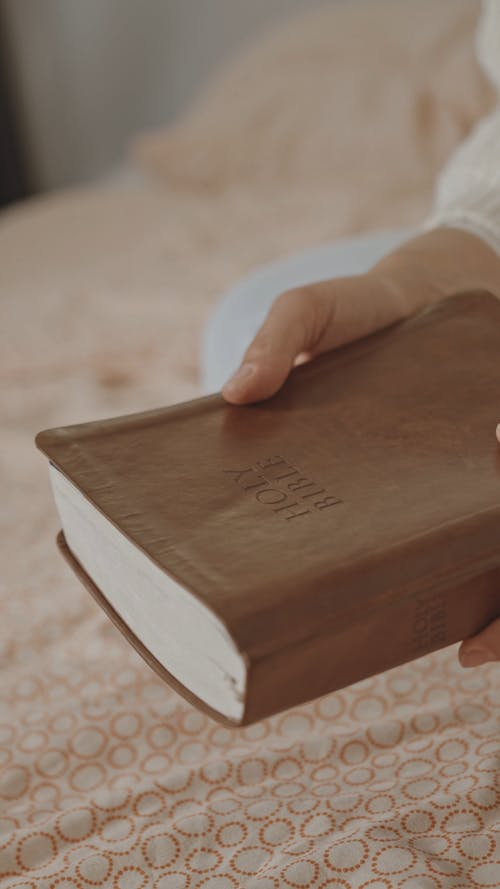 Close-Up View of a Person Opening a Bible