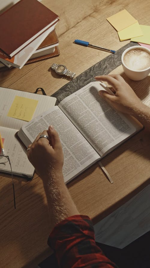 Top View of a Man Reading Holy Bible on his Study Table