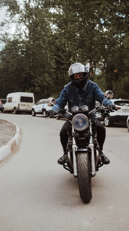 Man in Blue Denim Jacket Driving His Motorcycle