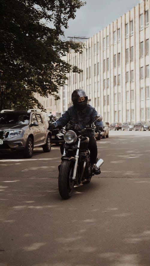 Man in Blue Denim Jacket Driving His Motorbike