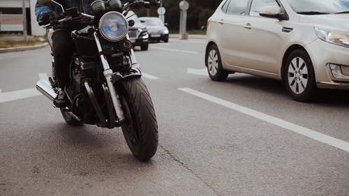 Man Driving His Motorcycle on Road