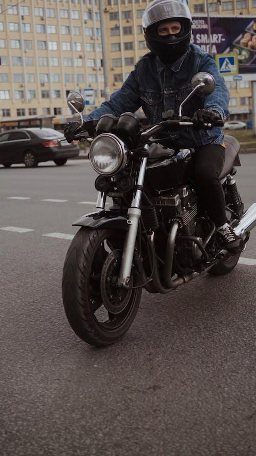 Man in Blue Denim Jacket Driving His Motorcycle on Road