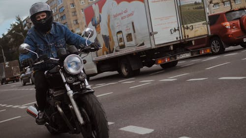 Man in Denim Jacket Riding His Motorcycle on Road