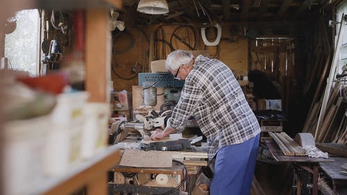 Old Aged Carpenter Working with Machines