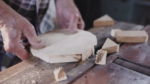Man Shaping Wooden Piece in Circular Shape