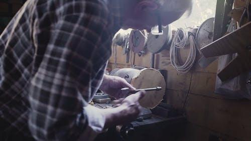 Man Fixing a Circular Block to Smooth it's Edges