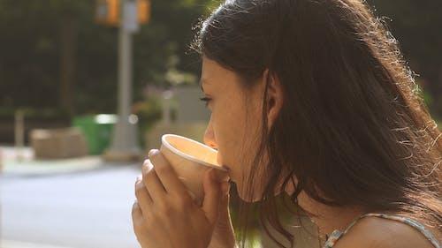 Woman Drinking a Coffee on the Roadside