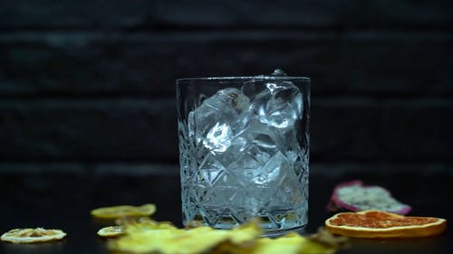 An Alcoholic Beverage Being Poured into a Glass with Ice