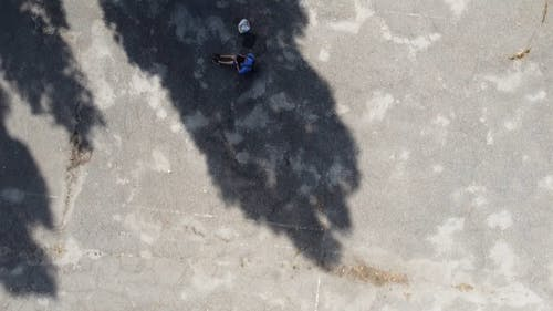Aerial View of Man Sitting in a Concrete Pavement nearby Housing Society