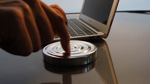 Man Playing with Fidget Spinner and Works on Laptop