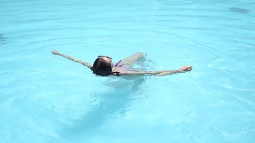 Woman in Purple Bikini Swimming in the Pool