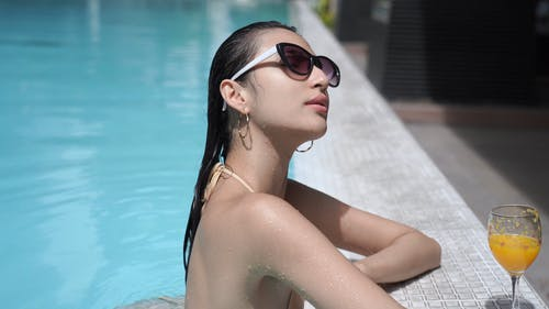 Woman Wearing Sunglasses While Relaxing in the Pool