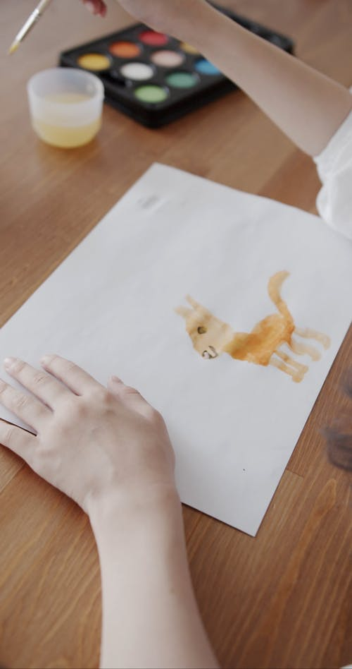 Person Using Watercolor for Painting in the White Paper