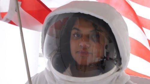 Frau In Einem Raumanzug, Der Eine Flagge Hält