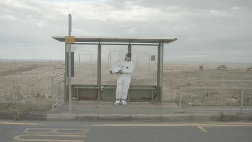 Astronaut Wartet An Einer Bushaltestelle