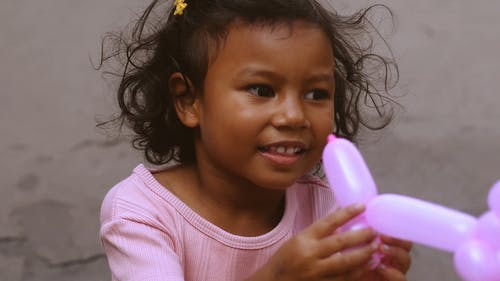 Cute Little Girl Playing with Balloon Animal Toy