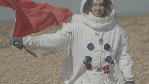 Mann, Der Einen Raumanzug Trägt, Der Eine Flagge Schwenkt