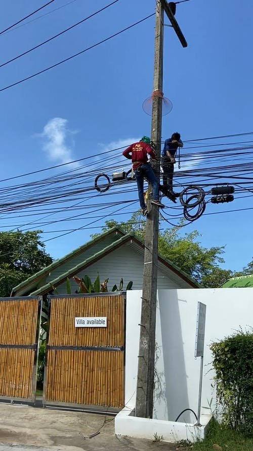 Two Men On The The Electric Post Fixing Cable Wires