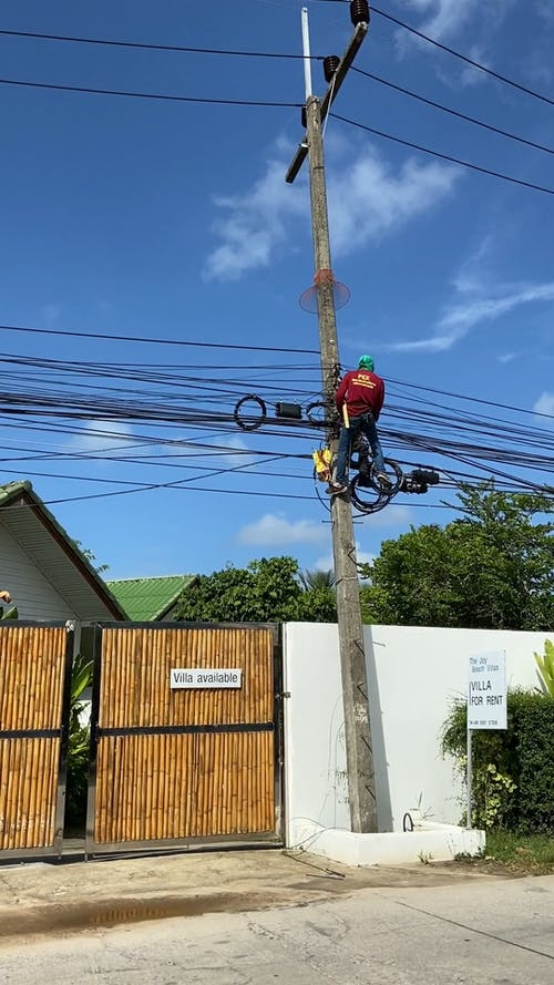 Men Up In The Electric Post Fixing The Lines