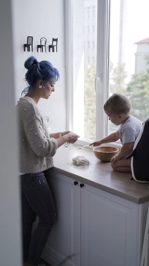 Mother and Child Standing at the Table