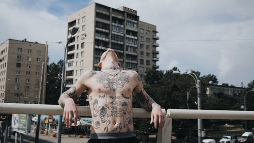 Tattooed Man Standing on Bridge Shirtless