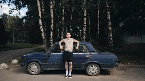 Topless Man Standing by an Old Car