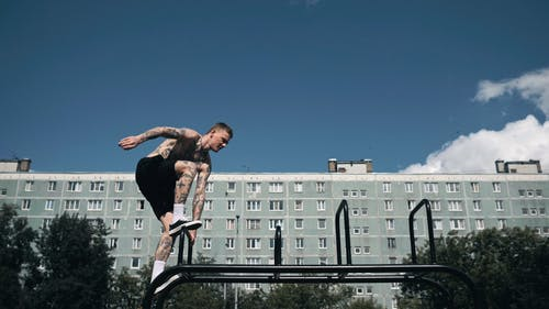 A Shirtless Man Doing Parkour Outdoors