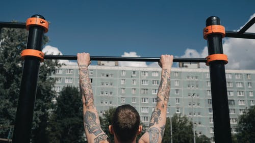 A Shirtless Person Doing Pull-Ups Outdoors