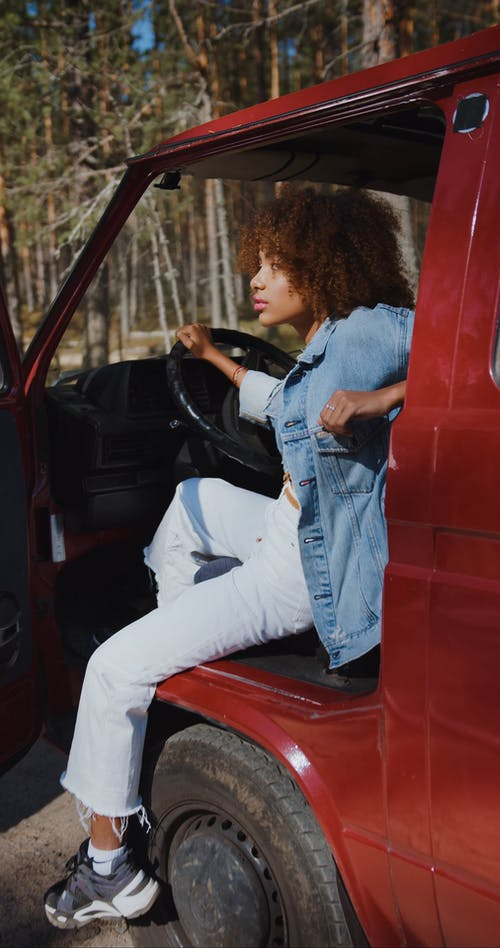 Young Woman Sitting in Pickup Truck Looking at Camera