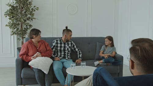 Parents Talking to Their Daughter while Sitting on Couch