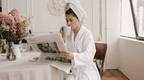 Woman Having Breakfast While Reading a Newspaper