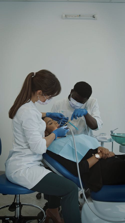 Female Dentist and Assistant Working with Patient
