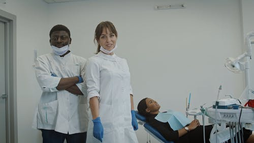 Female Dentist and Assistant Looking at Camera
