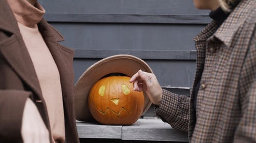 Women Discussing About a Carved Pumpkin