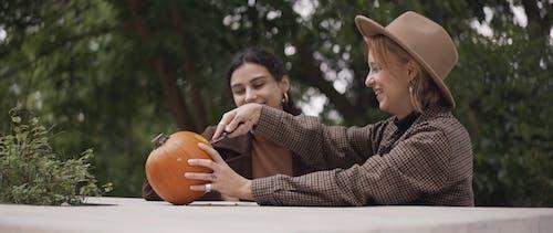 Two Beautiful Women Carving Pumpkin