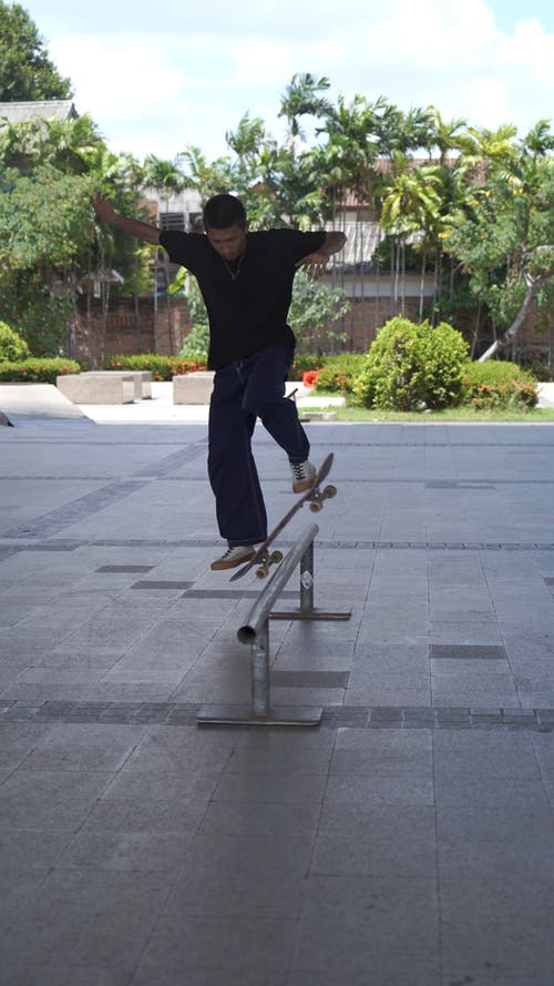 A Skateboarder Doing a Grind Trick on the Rail