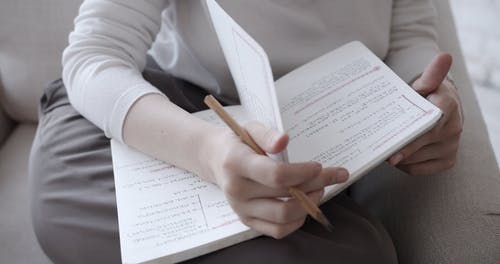 A Person Writing on a Notepad