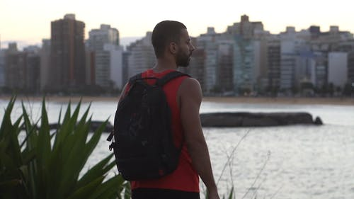 Shallow Focus of Man With Backpack Standing Outdoors
