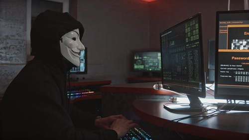 A Person Wearing a Guy Fawkes Mask While Using His Computer