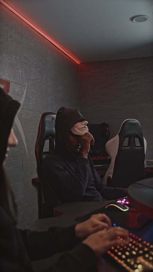 Two Persons Wearing a Guy Fawkes Mask While Using Their Computers