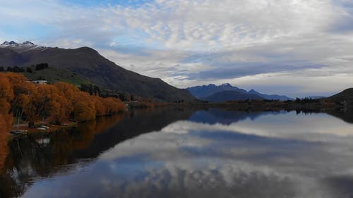 Beautiful Scenery of a Calm Lake Across the Mountains Under Cloudy Sky